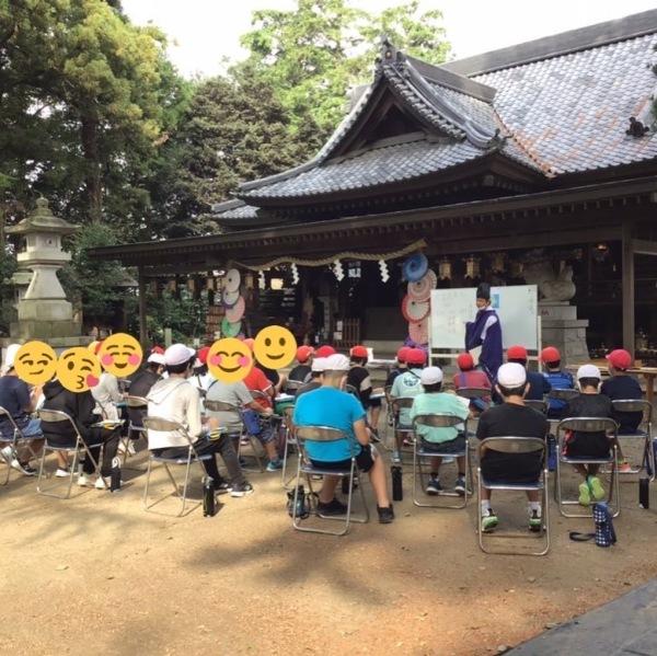 拝殿前にて宮司が歴史を説明 沢山メモをとる児童たち